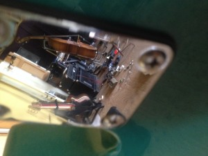 A lot of basses reflected in the neck plate of a bass.